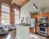 View of the Kitchen at Alpha Mill Apartments, tall ceilings, kitchen island, and long windows